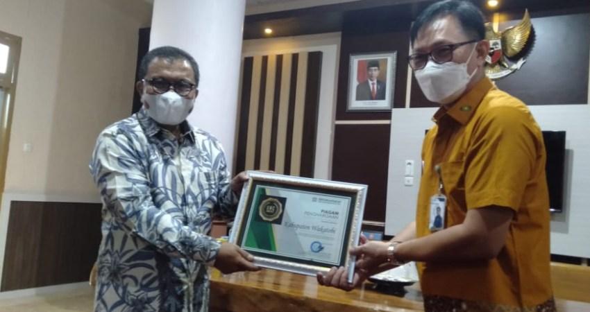 Bupati Wakatobi Arhawi saat menerima Piagam BPJS dari Deputi Direksi Wilayah Sulselbartramal) Dr. Beno Herman, di Wakatobi, Jum'at (25/06/2021).
