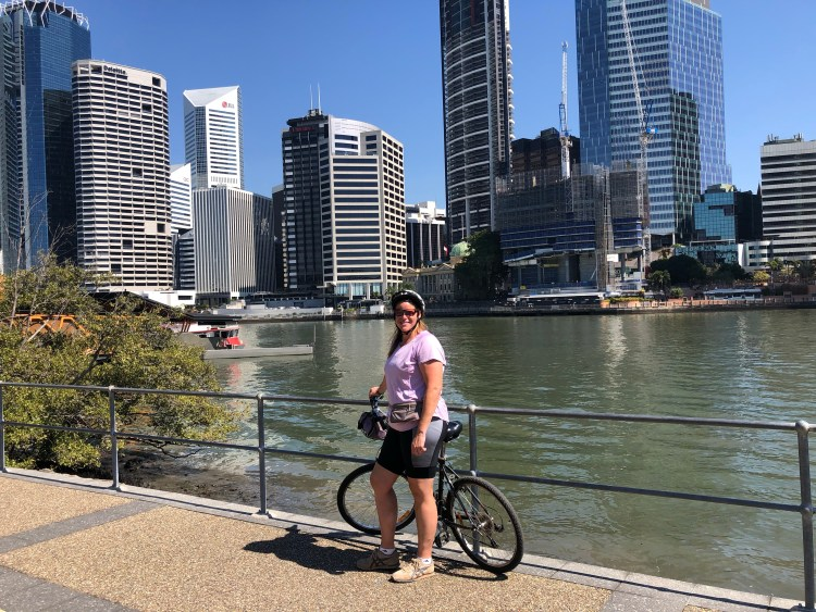 woman on bike with city in background