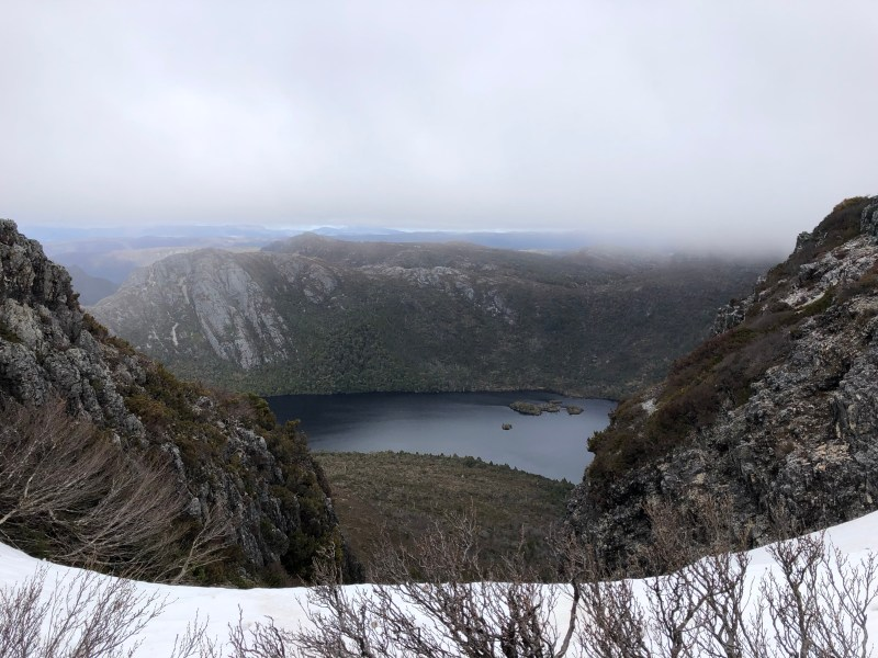snow on mountain peak with lake in background