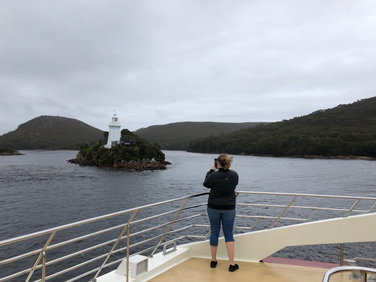 woman taking picture of lighthouse