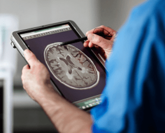 Medical tech uses a medical tablet to examine a scan