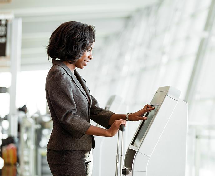 Woman using a public kiosk at an airport