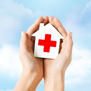 Cupped hands in front of a cloudy background holding a small white house with a red cross on it