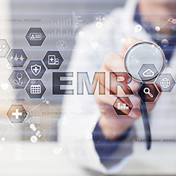 Doctor holding up a stethoscope to a digital display that says EMR