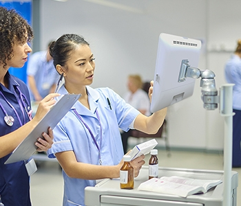 Healthcare professional uses a touchscreen medical computer on a cart