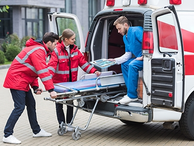 Healthcare professional using a rugged medical tablet to assist two EMTs