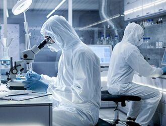 Two lab technicians working in a clean room environment