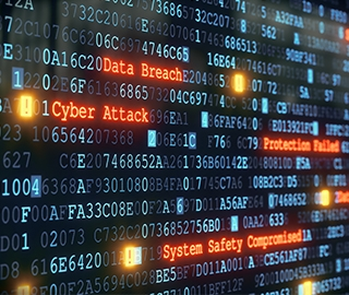 Computer monitor filled with code and highlighted phrases, including Data Breach, Cyber Attack, System Safety Compromised