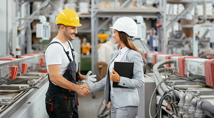 Factory engineer shakes hands with the foreman in the factory