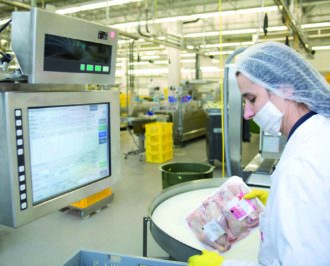 Factory worker in a food processing plant using an industrial computer