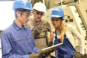 Metalworker with training people using industrial tablet