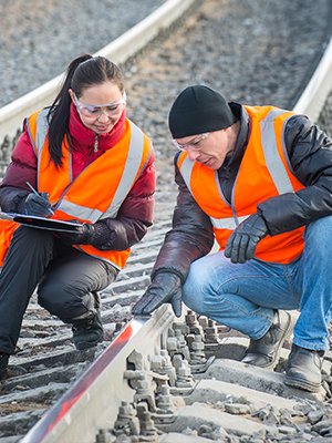 Two logistics workers at a train depot inspect train tracks with a rugged tablet