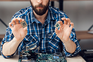 Man holding two computer chips as he disassembles a computer