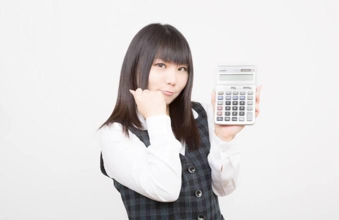 電卓を使い電験3種の計算問題を解こうとする女性。