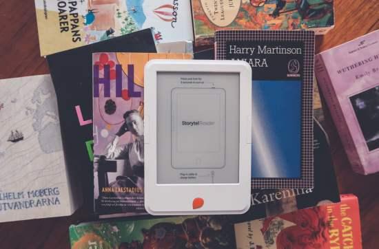 En vit läsplatta som heter Storytel Reader som ligger på en hög med vanliga böcker