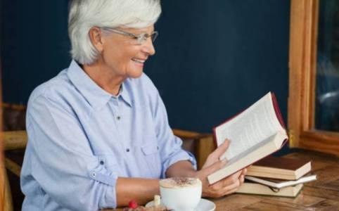 Літня жінка читає книжку й усміхається