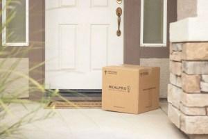 brown cardboard box beside white wooden door