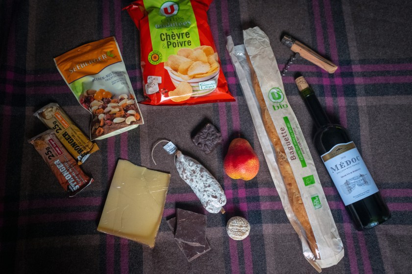 My food stash at the start of the trip: local cheeses and sausage, pear, bread, wine, chocolate, potato chips, trail mix.