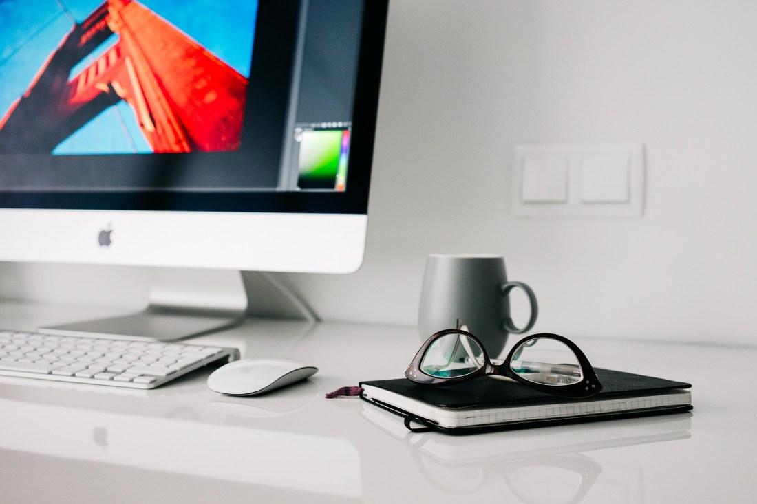 ordinateur mac avec un mug et un bloc note