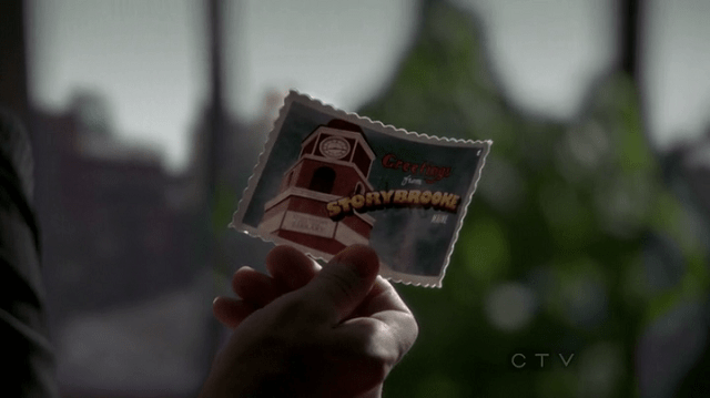 "a screencap of the front of a postcard that reads ""greetings from storybrooke maine"""