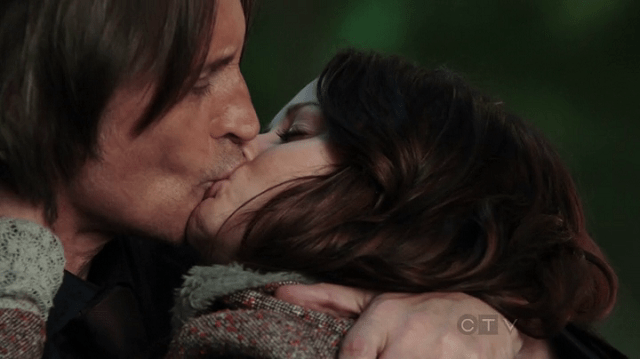 a screencap of rumpelstiltskin/mr gold kissing belle