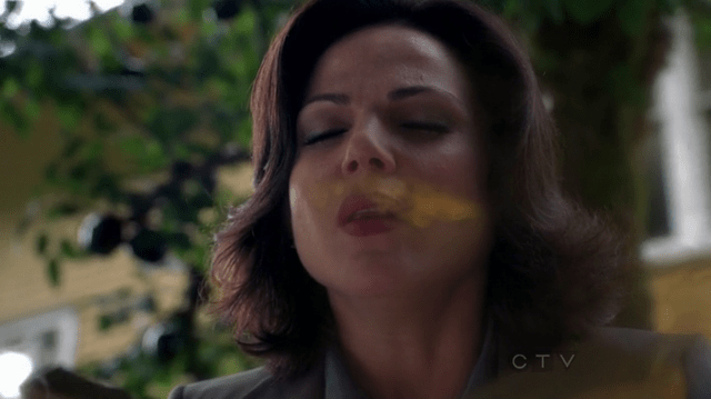 a screencap of regina mill (played by Lana Parrilla) breathing in some magic