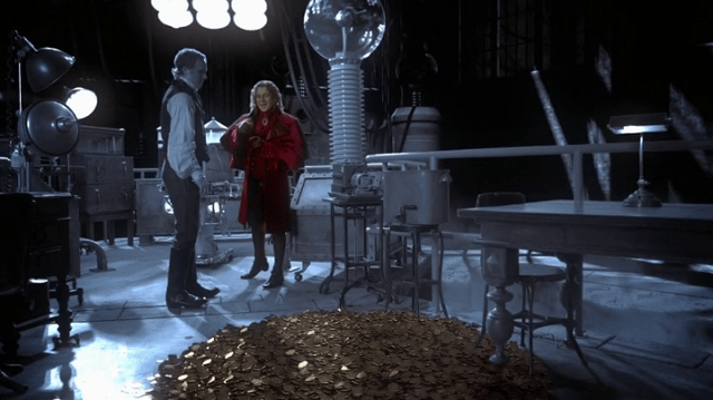 rumpelstiltskin (played by robert carlyle) pours a pile of gold on the floor of the black and white laboratory of frankenstein (played by david anders)