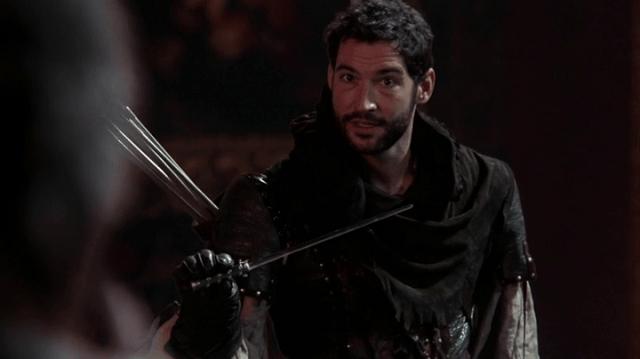 a screencap of robin hood (played by tom ellis) stealing a magic wand from rumpelstiltskin