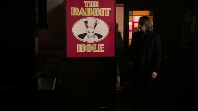a screencap of rumpelstiltskin (played by robert carlyle) standing next to the rabbit hole sign