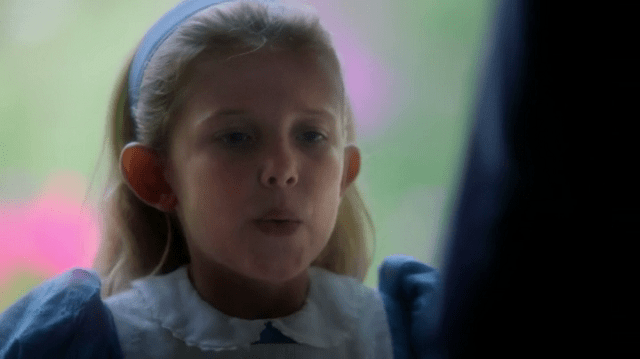 a screencap of a young alice (played by millie brown)