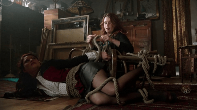 a screencap of ariel (played by joanna garcia swisher) untying herself and belle (played by emilie de ravin)