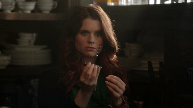 a screencap of ariel (played by joanna garcia swisher) entranced by a thingamabob or corkscrew