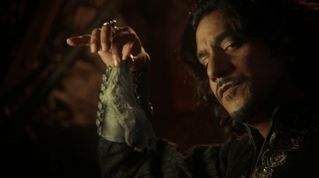 a screencap of jafar (played by naveen andrews) holding aloft the white rabbit's severed foot