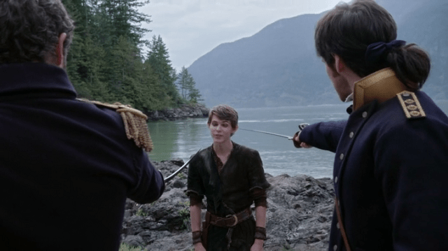 a screencap of captain liam jones (played by bernard curry) and lieutenant killain jones (played by colin o'donoghue) pointing their swords at peter pan (played by robbie kay)