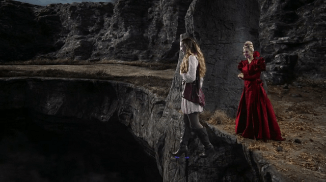 a screencap of alice (played by sophie lowe) crossing the great divide while the red queen (played by emma rigby) looks on