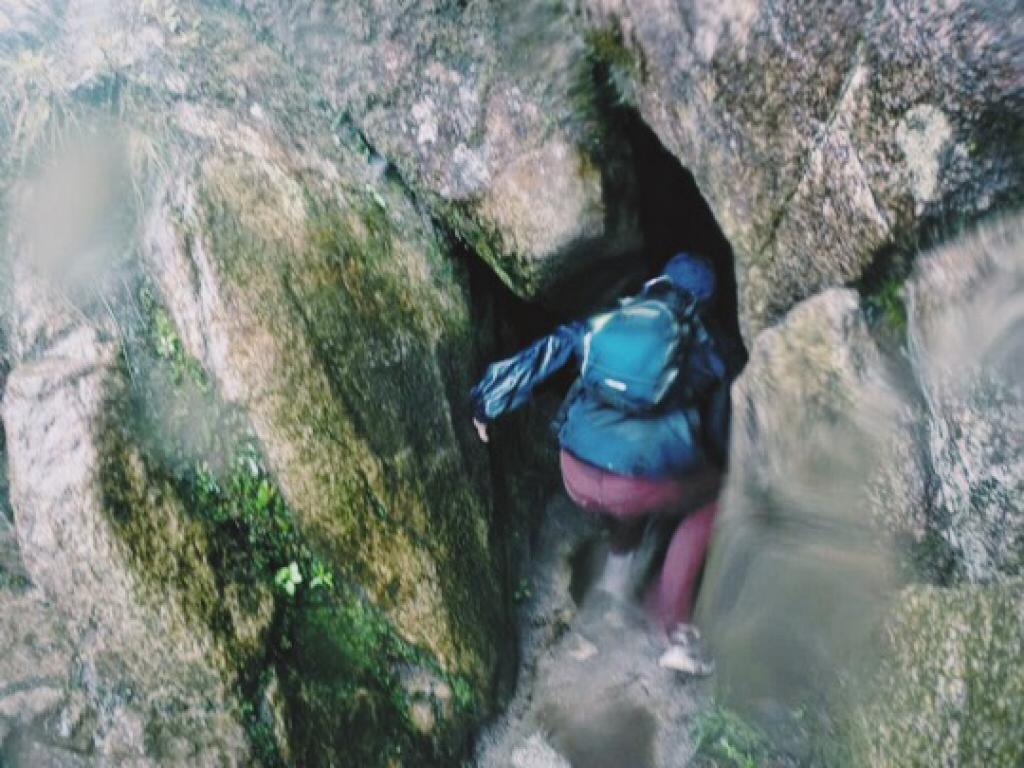 Ben climbing through cave at Huayna Picchu