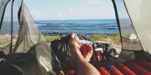 mans som ligger på luftmadras paa camping turen