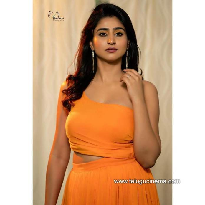 Varshini in an orange coloured outfit