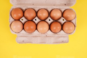 Brown eggs in a tray on yellow