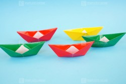 Colorful origami paper ships on blue