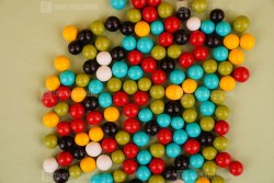 Colorful round dragee candies on green background