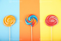 Different tasty colorful candies on pastel color background