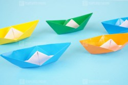 Paper boats on light blue surface