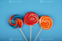 Spiral colored round lollipops on blue background