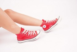 Red sneakers on girl sits on white background
