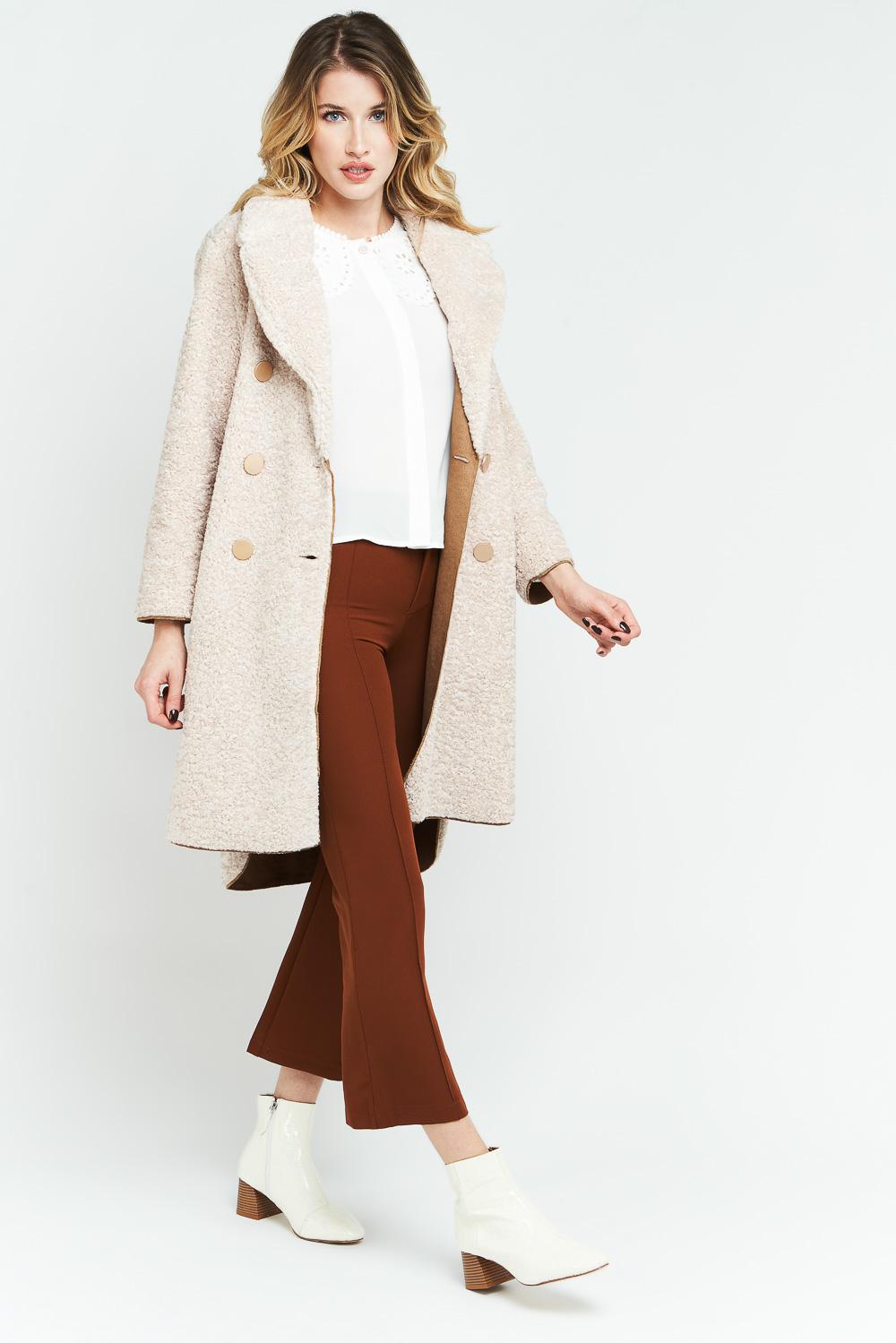 Femme en manteau long pantalon marron sur fond gris