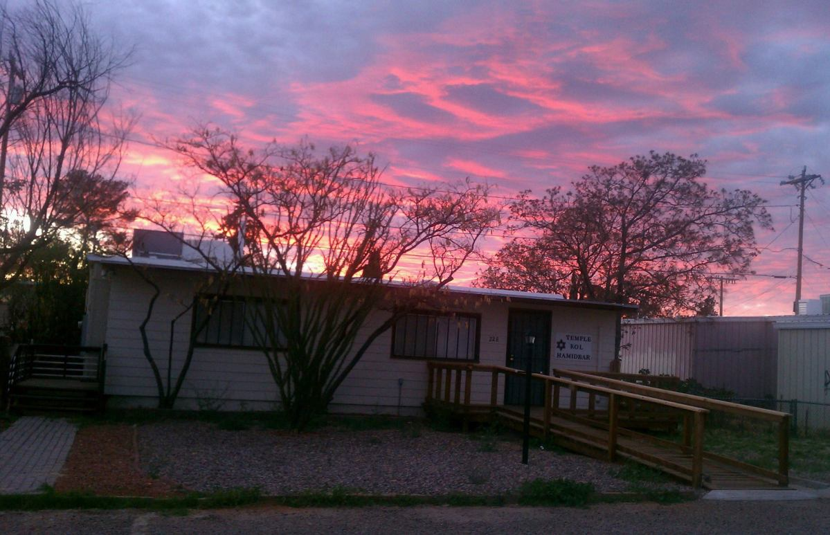 An orange and vermillion sunset behind Temple Kol Hamidbar, Cochise County's First and Only Synagogue