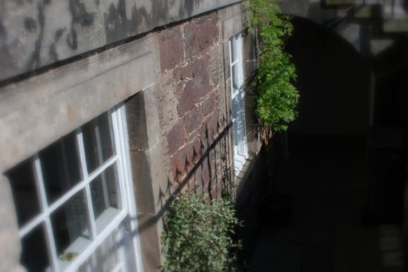 The arrow head railings reflect on the red sandstone, the more typical stone employed in Dunbar building construction with ashlar used in finer buildings