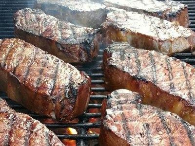 Steaks grilling over charcoal