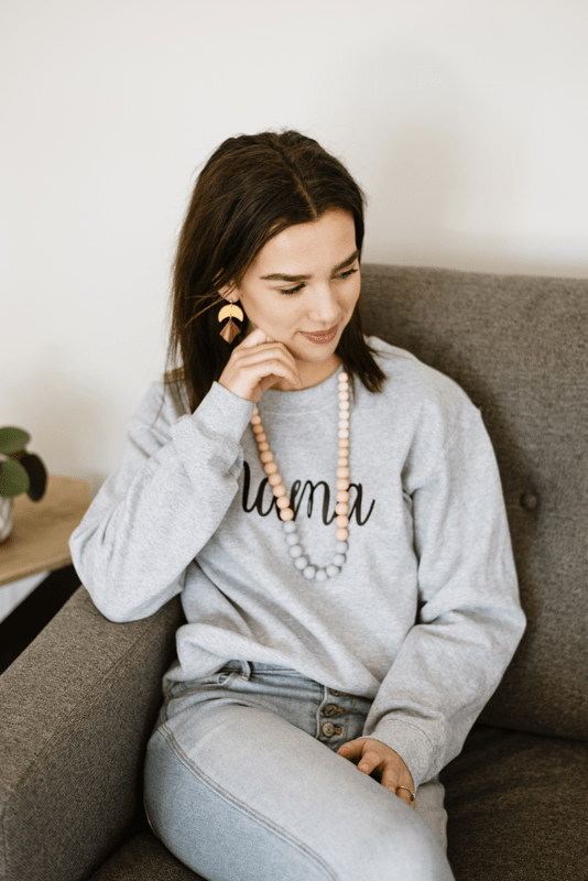 Woman sitting on a sofa wearing a toy necklace